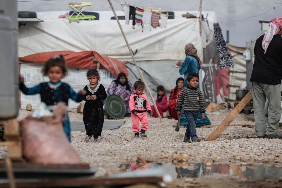 Photo: Young Syrian refugees walk through an informal settlement in the Bekaa Valley.  © UNHCR/Sam Tarling