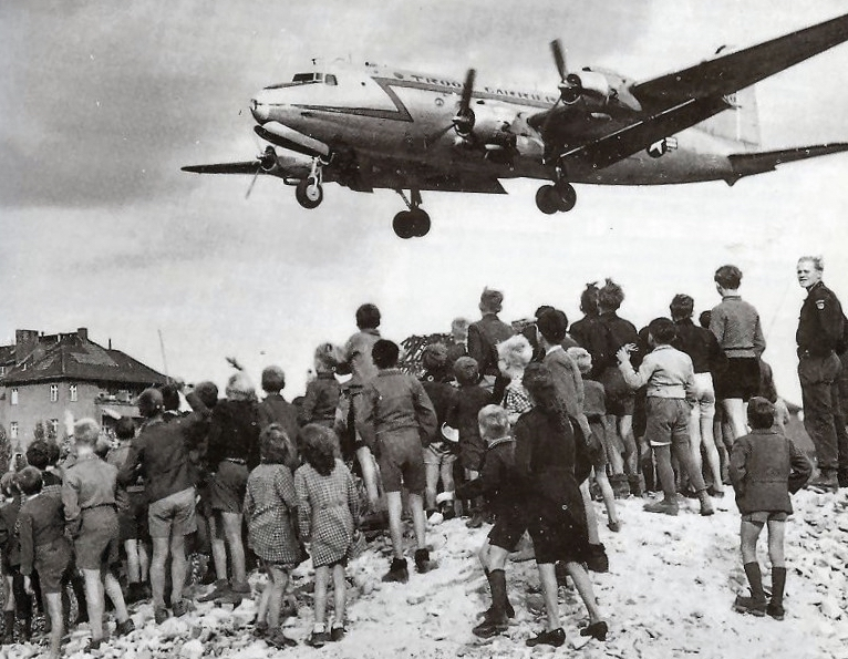 Photo: Citizens of Berlin watch a C-54 land at Berlin Tempelhof Airport in 1948 (US Air Force via Wikimedia Commons)