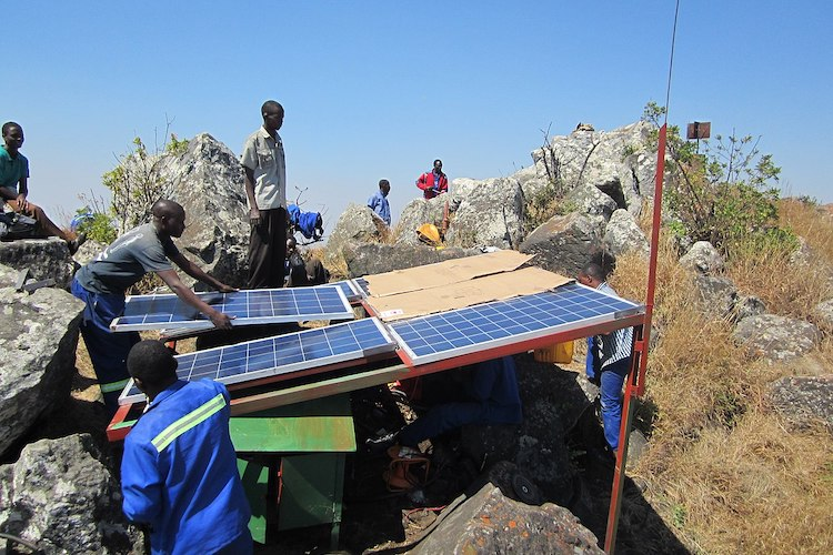 Photo: Workers construct a solar panel array structure in Malawi. CC BY-SA 4.0