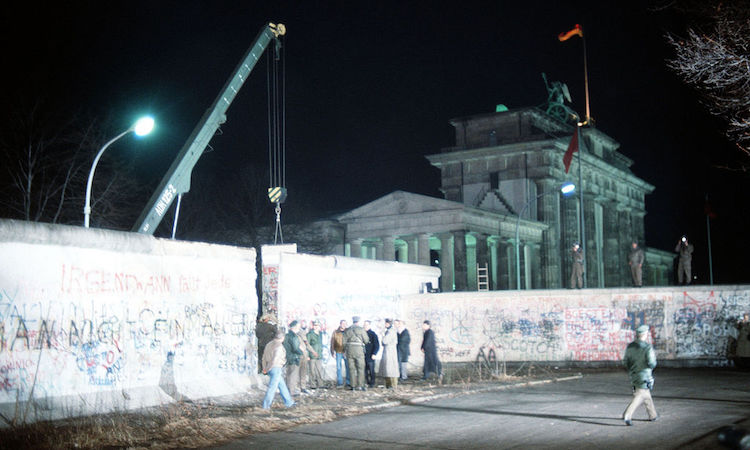 Photo: A crane removes a section of the Wall near Brandenburg Gate in Berlin on 21 December 1989. Source: Wikimedia