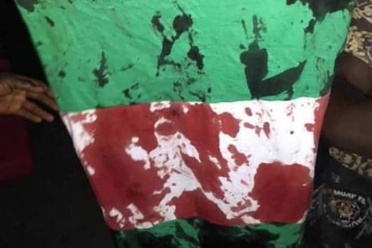 Photo: Bloodied Nigerian flag from after the massacre. CC BY-SA 4.0