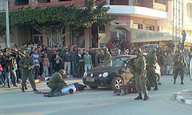 Photo: The Tunisian National Army restored order in absence of police services. The picture shows a civilian who was stopped because of a weapon in his car. 15 January 2011. CC BY-SA 3.0