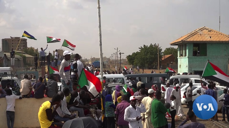 Photo: Sudanese protestors gather in front of government buildings in Khartoum to celebrate the final signing of the Draft Constitutional Declaration between military and civil representatives in August 2019. VOA-Public Domain.