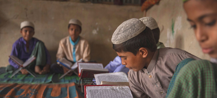 Photo: A boy reads from his textbook in a camp in Cox's Bazar, Bangladesh. Credit: UNICEF Patrick Brown