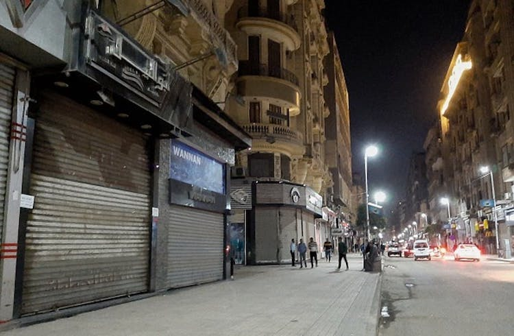 Photo: A deserted street in Cairo after the government ordered the closure of shops, restaurants and cafes. Credit: Ziad Ahmed/NurPhoto via Getty Images