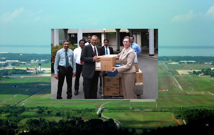 Photo (against the backdrop of Bandaranaike International Airport): U.S. Ambassador to Sri Lanka, Alaina B. Teplitz (right front) presenting a branded donation of Dupont Tyvek coveralls, nitrile gloves, heavy duty work gloves, boot covers, and cleaning supplies to Major General (Rtd) GA Chandrasiri (left in front), Chairman of the Civil Aviation Authority of Sri Lanka on behalf of the American people. The equipment will help protect airport personnel and prevent the spread of COVID-19. The donation is part of U.S. efforts to assist Sri Lanka.