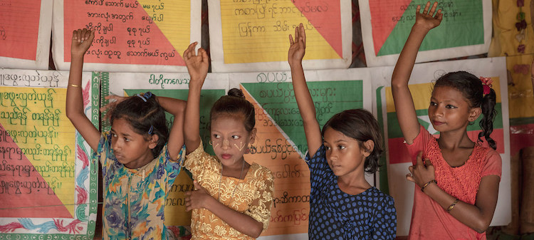 Photo: Children raise their hands to answer a question in class at a UNICEF learning space in Cox's Bazar, Bangladesh. (8 July 2019). Credit: UNICEF Patrick Brown