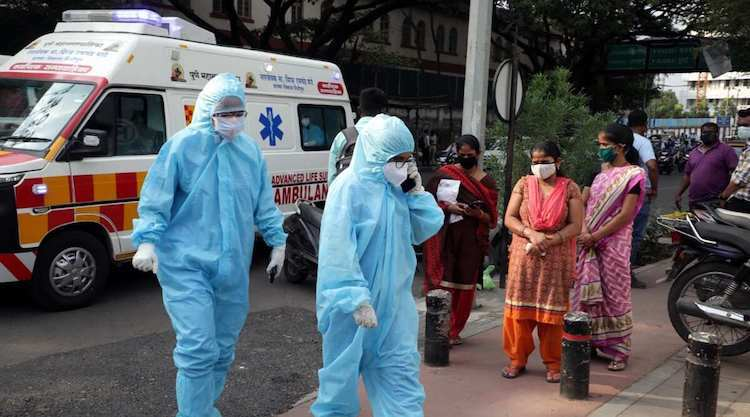 Photo: Health workers in front of the Jumbo Covid facility in Pune on May 5. (Express photograph by Arul Horizon)