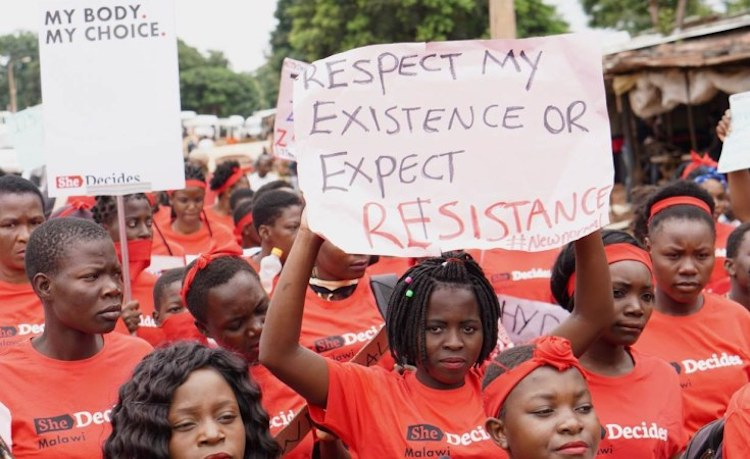 Photo: Some 90 young women took to the streets in a silent march through Lilongwe, Malawi's capital, on March 2. Credit: AllAfrica | Alice McCool/Thomson Reuters Foundation.