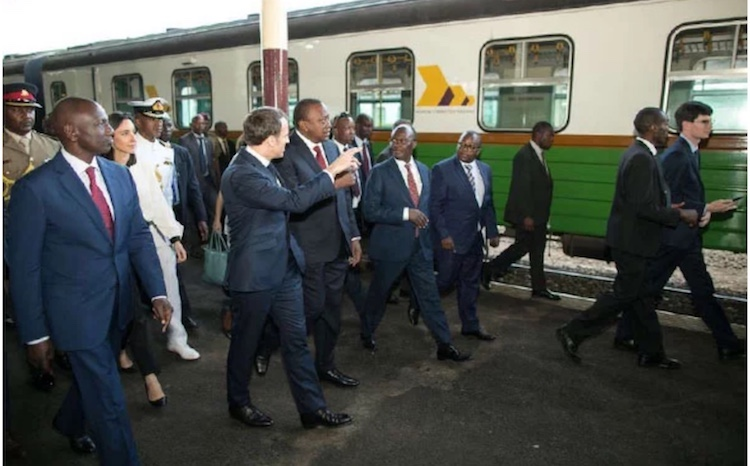 Photo: Kenyan Deputy President William Ruto (left), French President Emmanuel Macron and his Kenyan counterpart Uhuru Kenyatta tour the Nairobi Central Railway station during a briefing tour on the progress of the proposed commuter rail service to JKIA on March 13,2019. Credit: Samuel Miring'u