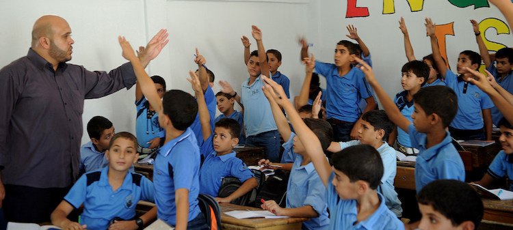 Photo: Palestinian boys raise their hands during one of the first classes of the new academic year, at a school in Gaza supported by UNRWA. UN Photo/Shareef Sarhan