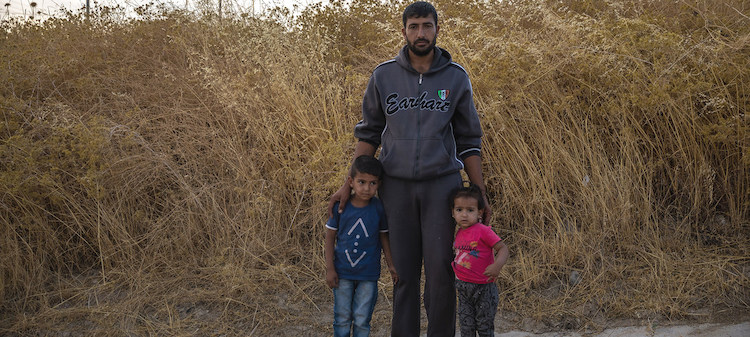 Photo: A Syrian father stands with his children at Bardarash camp in Duhok, Iraq, a day after arriving. © UNHCR/Hossein Fatemi.