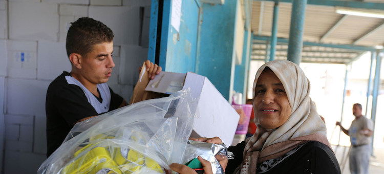 Photo: A Palestine refugee woman receives food assistance at the UNRWA Khan Younis Distribution Centre in Gaza. UNRWA/Tamer Hamam.